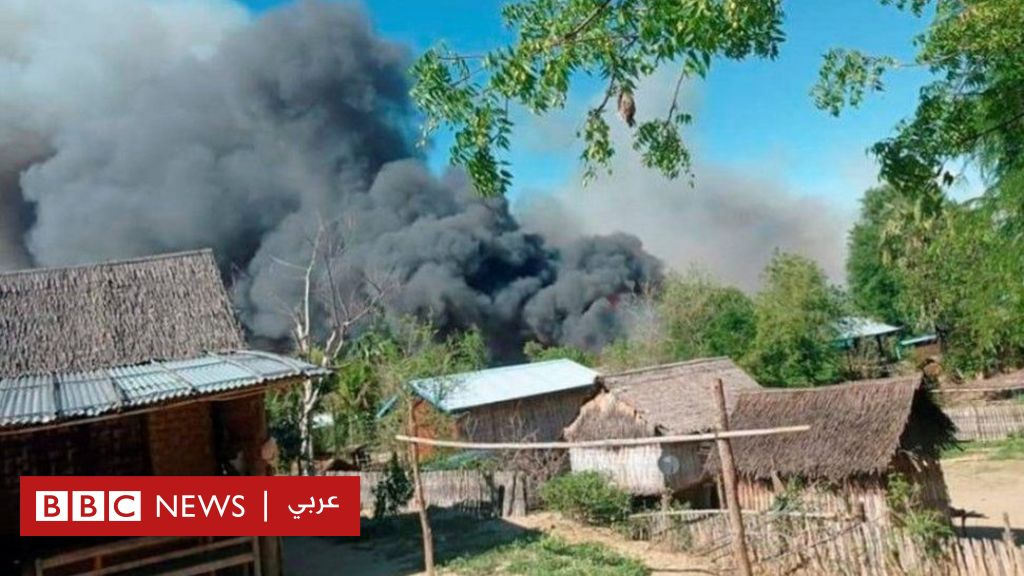 A burning village in Myanmar, fingers pointing at the military