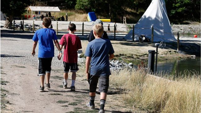Boy Scouts of America walking around a campground.