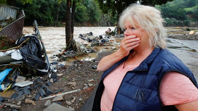 A German woman looks in shock at the waters of a river that has overflowed its banks