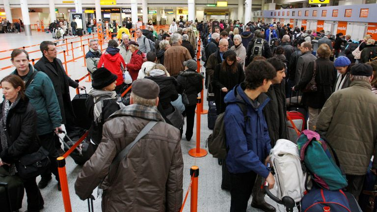 Passengers line up at check-in counters at Gatwick Airport