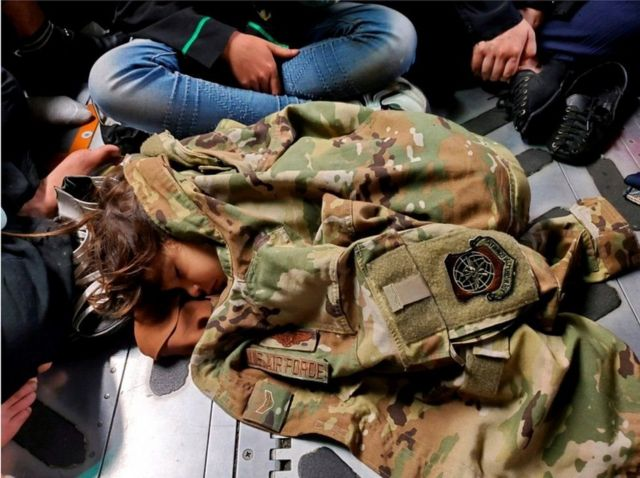 A sleeping girl is wrapped in a military jacket