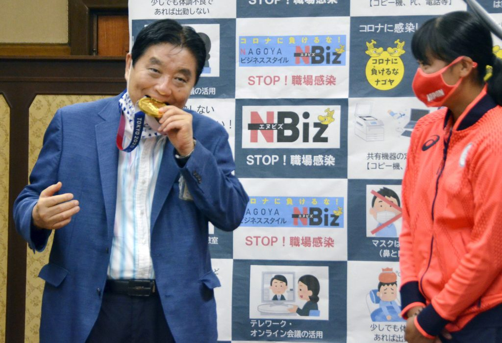 A Japanese official apologizes after biting a gold medal, and the winner accepts its exchange